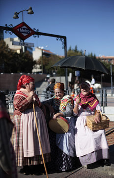Women wearing traditional costumes laugh as they take a break during a sheep parade in central Madrid