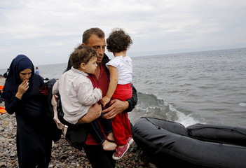 A Syrian refugee family walks towards a nearby village upon arriving on the Greek island of Lesbos