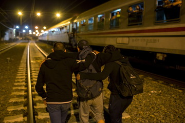 Migrants make their way to board a train as they wait to depart from the railway station in Tovarnik