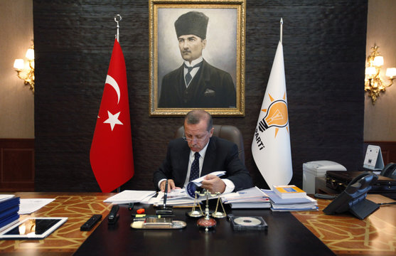 Turkey's Prime Minister Erdogan, with a portrait of modern Turkey's founder Ataturk in the background, works at his office at the AK Party headquarters in Ankara