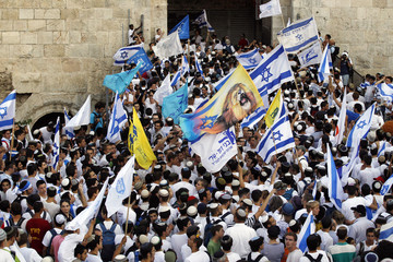 Youths wave Israeli flags during a parade marking Jerusalem Day, at Damascus Gate in Jerusalem's Old City
