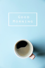 Text Good Morning White hot coffee in cup on blue background,copy space,Top view,flat lay