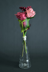 fiori di stoffa variopinti dentro un vaso tubolare in vetro trasparente