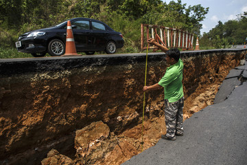 An officer measures a drop on a section of a highway road, which was damaged by Monday's earthquake in Chiang Rai, in northern Thailand