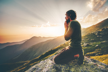 Man praying at sunset mountains Travel Lifestyle spiritual relaxation emotional concept vacations outdoor harmony with nature landscape Fotomurales