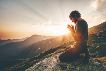 Man praying at sunset Wall mural