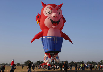 Spectators take pictures and watch the Burnie the Little Devil hot air balloon as it takes off during the Philippine International Hot Air Balloon Fiesta in Pampanga province