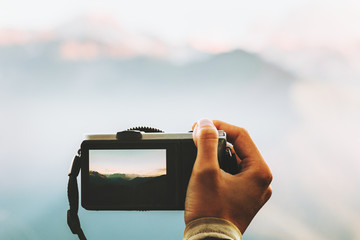 Hand with photo camera taking shot of mountains landscape outdoor Travel Lifestyle adventure summer vacations