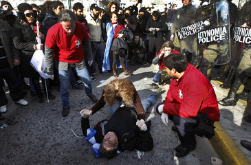 Medics try to help an anti-austerity protester, who lies unconscious after he was injured by police, in Athens