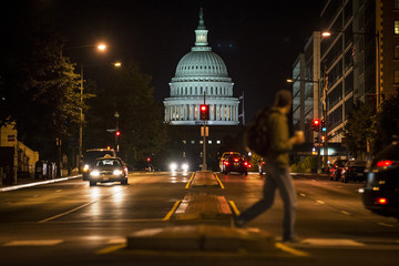 A man walks across North Capitol Street in front of the U.S. Capitol building in Washington