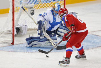 Russia's Smolina tries to score against Finland's goalie Raty during the first period of their women's ice hockey classification game at the Sochi 2014 Winter Olympic Games