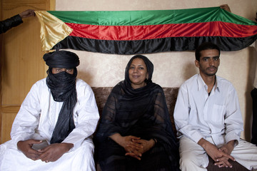 MNLA political bureau official Intalou poses for a picture in front of Azawad flag