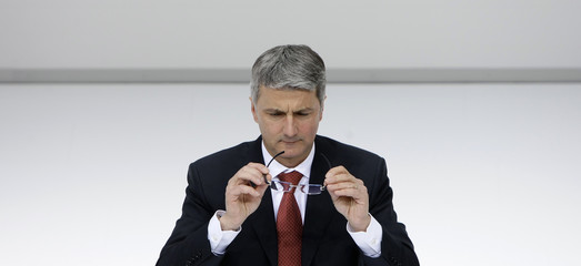Audi CEO Stadler removes glasses during annual news conference in Ingolstadt