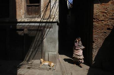 A woman walks along an alley in Kathmandu