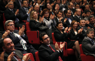New chairman of the Istanbul Stock Exchange Turhan applauds during a handover ceremony at the bourse in Istanbul