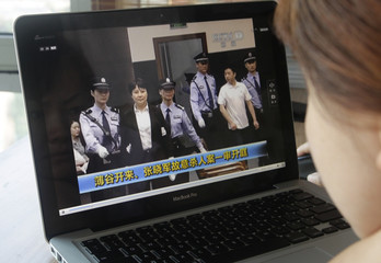 A woman watches a CCTV video showing Gu Kailai being escorted into the court room at Hefei Intermediate People's Court, on a laptop in Beijing