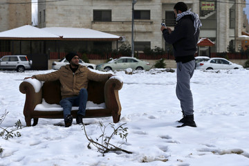 People pose for pictures after a heavy snowstorm in Amman
