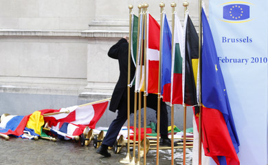 An official walks over fallen flags while EU heads of state arrive at an informal summit in Brussels