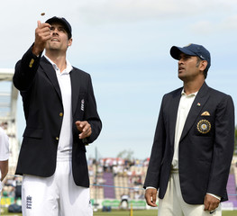 England's captain Cook tosses the coin as India's captain Dhoni watches before the third cricket test match at the Rose Bowl cricket ground, Southampton