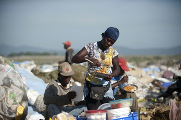 A woman sells food to garbage pickers in the Duquesa dump in Santo Domingo