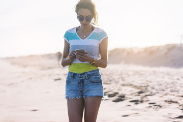 Hipster girl hold on smart phone gadget in sand coastline beach, mock up of blank screen. Traveler using in female hand mobile on background seascape horizon. Tourist look on blue sun ocean