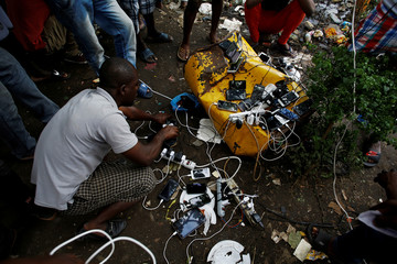 African migrants stranded in Costa Rica charge their phones at a makeshift camp at the border between Costa Rica and Nicaragua, in Penas Blancas
