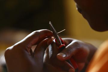 A woman makes a bead bracelet at the Uzima bead-making workshop in Nairobi
