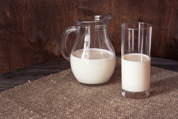 Milk in a glass and a glass jug on a wooden table