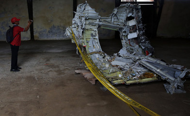 Man shoots video footage of part of the fuselage of crashed AirAsia Flight QZ8501 inside a storage facility at Kumai port in Pangkalan Bun