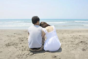 砂浜で寄り添う若いカップル