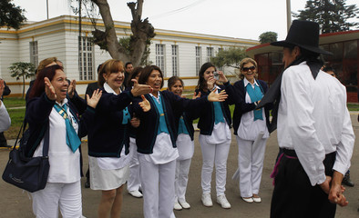 Health workers celebrate as patient parades during Independence Day celebrations at Larco Herrera psychiatric hospital in Lima