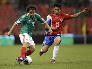 Mexico's Guardado battles for the ball with Costa Rica's Cubero during their 2014 World Cup qualifying soccer match in Mexico City