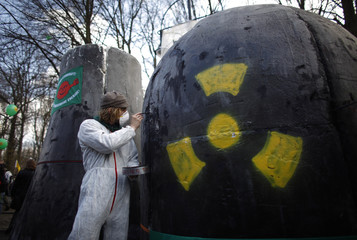An activist of Robin Wood paints mock-up of nuclear power station during protest in Berlin