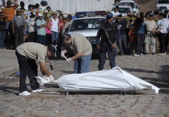 Forensic technicians prepare to remove a stretcher holding a bag containing several other bags with dismembered parts of human bodies in a neighborhood in Tegucigalpa
