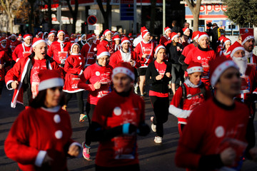 Runners dressed as Santa Claus take part in the 40th Christmas Corrida Race on the streets of Issy-les-Moulineaux, near Paris
