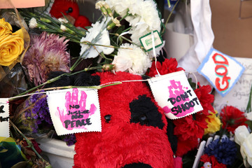 """Signs reading """"No justice, no peace,"""" and """"Don't shoot"""" are seen on a memorial in front of a Louisiana convenience store where Alton Sterling was killed by police in Baton Rouge"""
