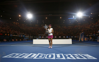 Li Na of China poses with The Daphne Akhurst Memorial Cup after defeating Dominika Cibulkova of Slovakia in their women's singles final match at the Australian Open 2014 tennis tournament in Melbourne