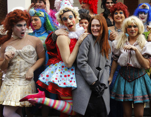 """Actress Moore poses with Hasty Pudding theatricals cast members as she is honored as the """"Hasty Pudding Theatricals Woman of the Year"""" in Cambridge"""