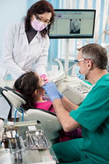 Young girl with on the first dental visit. Senior pediatric dentist with nurse treating patient teeth at the dental office. On the background screen with X-ray the patient's teeth. Dental equipment