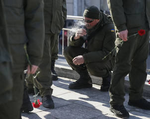A member of a Ukrainian National Guard battalion smokes before a ceremony in honour of the second anniversary of the battalion's creation and to commemorate members killed in the pro-Russian separatist conflict in eastern regions, in Kiev