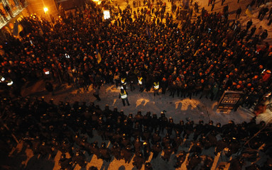 Pro-European integration protesters line up in front of riot police in Kiev