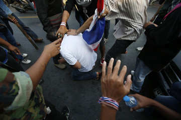 Anti-government protesters detain a man they suspect is spying on them outside a polling station in Bangkok