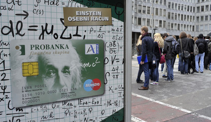 People stand next to an advertisement for Probanka in Ljubljana