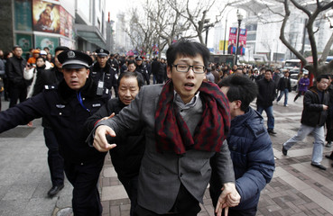 A man is arrested by police in front of the Peace Cinema in downtown Shanghai