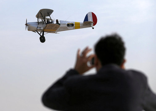An Egyptian man takes a picture for the biplane which flown by Cedric Collette and Alexandra Maingard glides by Egypt's iconic pyramids of Giza, on the second leg of their month-long journey through Africa in Cairo