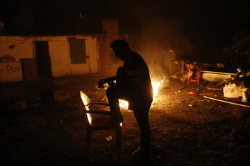 Miguel Cortes Vargas plays the guitar by a bonfire as he waits for his family's eviction and the demolition of several of their relatives homes in Madrid