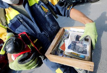 A firefighter carries a drawer with pictures and personal belongings following an earthquake in Amatrice, central Italy