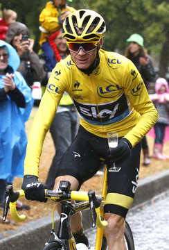 Team Sky rider Chris Froome of Britain, the race overall leader's yellow jersey, holds a glass of champagne as he cycles during the final 21st stage of the Tour de France cycling race