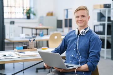 mann im büro mit notebook und kopfhörern