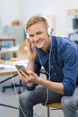 lächelnder mann im büro mit handy und kopfhörern